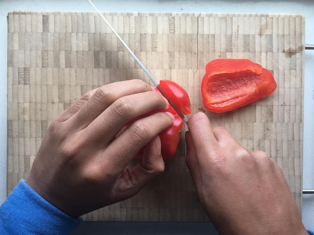 Een paprika die rond de pitten gesneden wordt