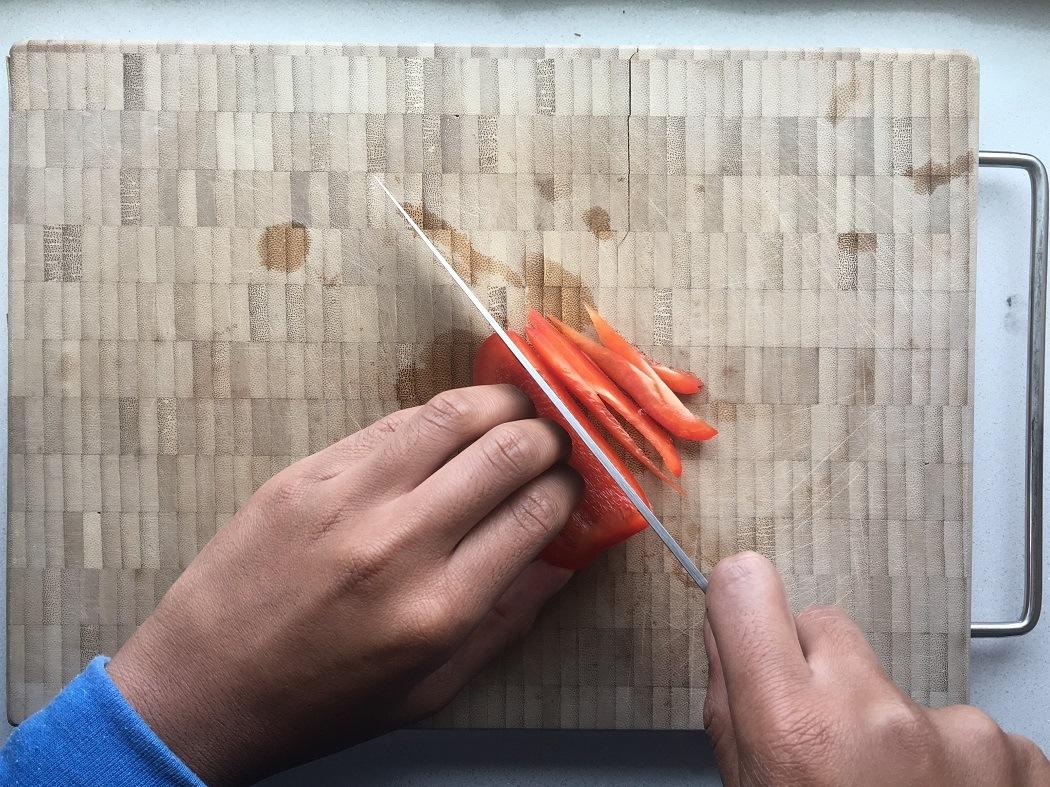 Een paprika die julienne gesneden wordt