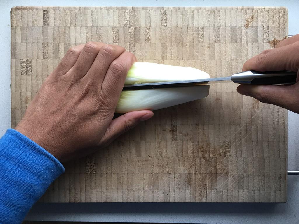 Een witlof die in twee helften gesneden wordt