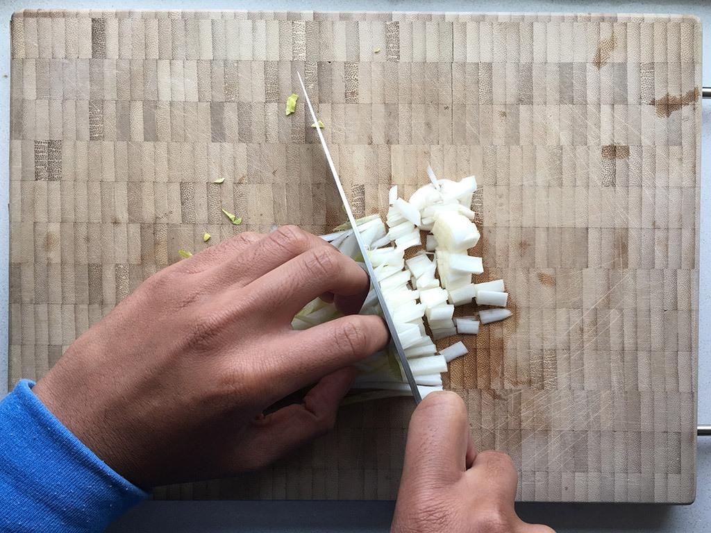 Een witlof die in blokjes gesneden wordt